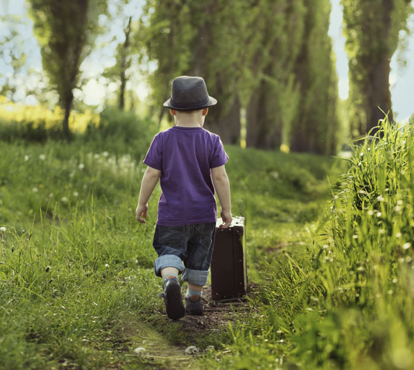 Little boy walking down path with suitcase