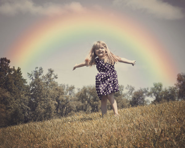 Little girl running under rainbow