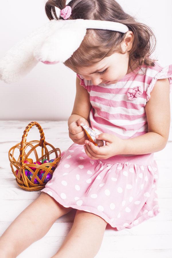 Little girl peeling chocolate egg