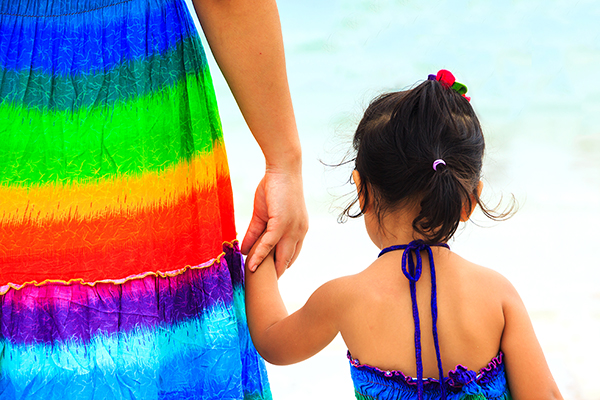 Mother holding the hand of her daughter on the beach