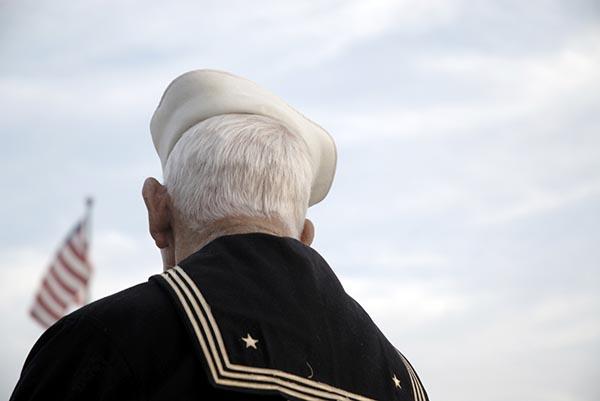 Veteran sailor looking at flag