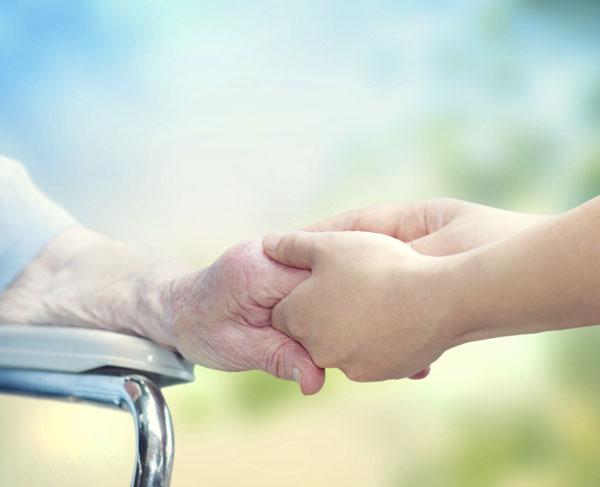 Young caretaker holding hands of elder woman