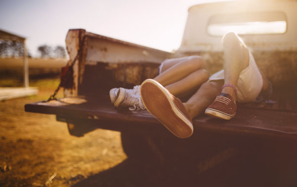 Couple lying in the back of old pickup truck
