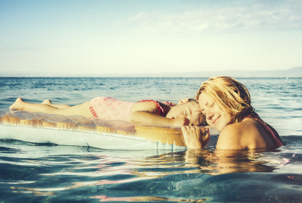 Mother and daughter floating in ocean and sunshine