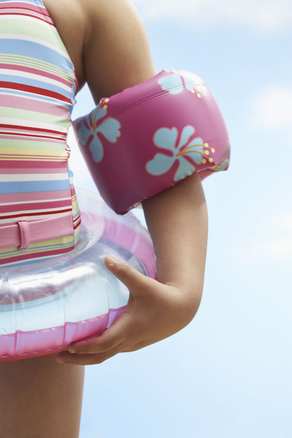 Little girl wearing floaties and swim ring