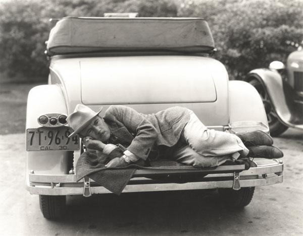 Man sleeping on bumper of car