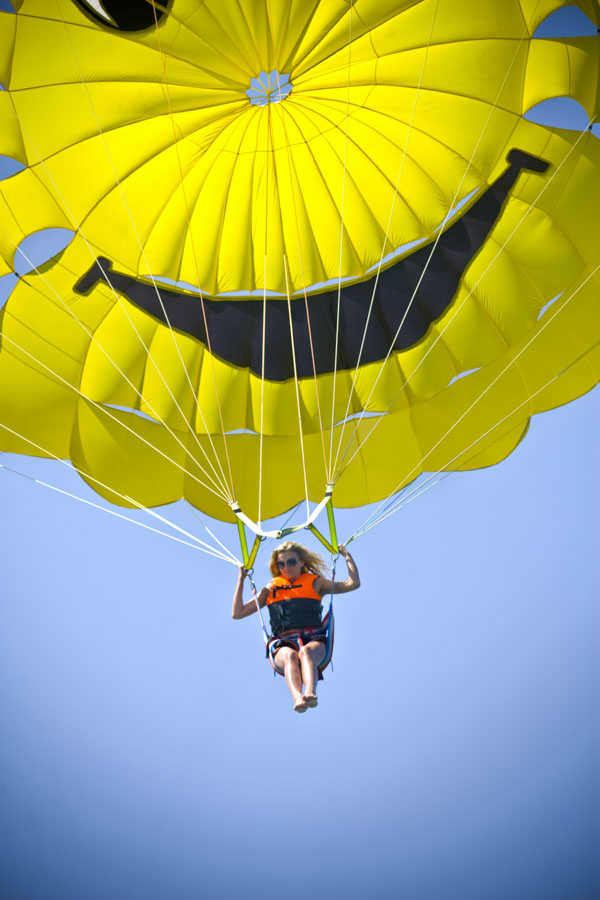 Parasailing woman with happy face parachute