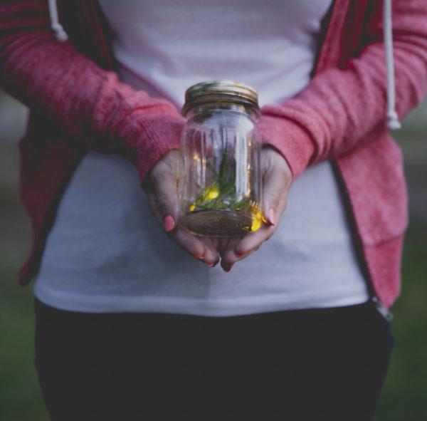 Woman holding fireflies in jar
