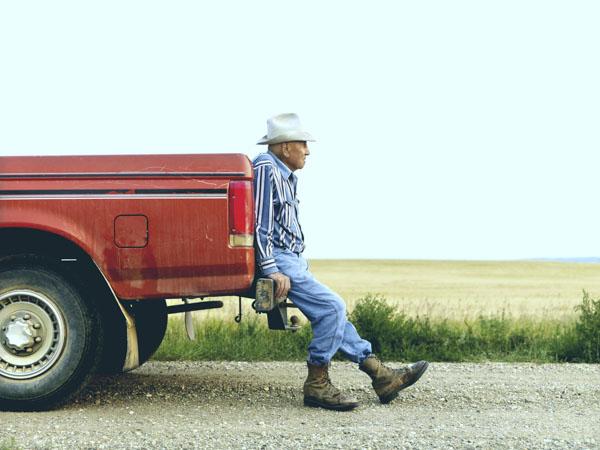 Old man sitting on truck bumper