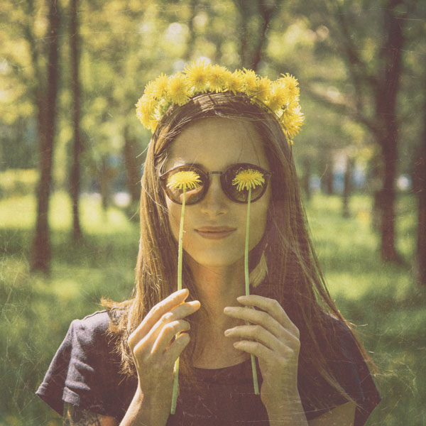 Woman holding dandelion flowers to her eyes