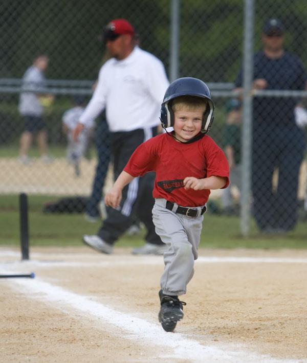 Little baseball player running