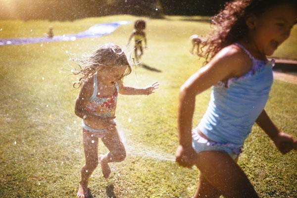 Little girls running through water from the garden hose