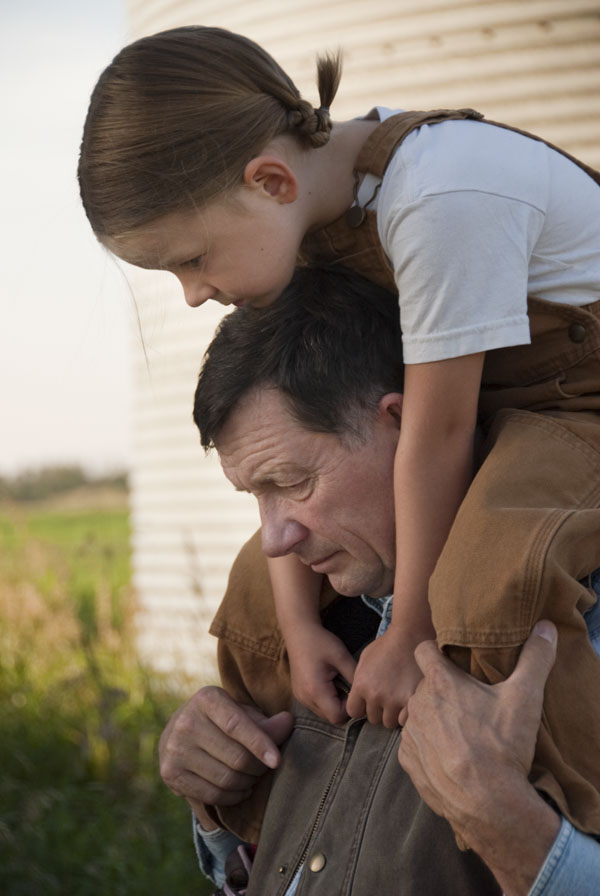 Little girl on her grandfather's shoulders on farm