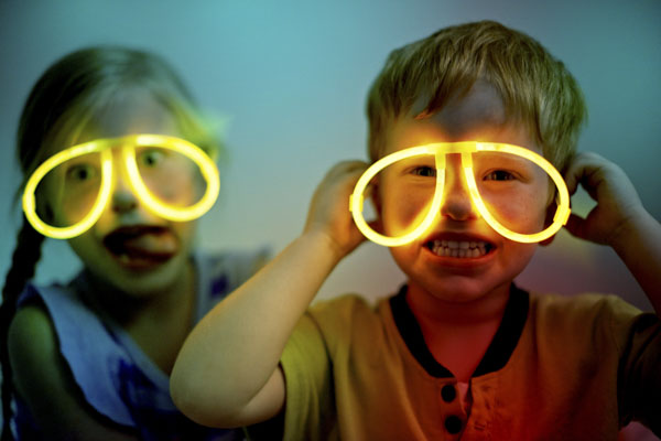 Adorable boy and girl with glow in the dark glasses