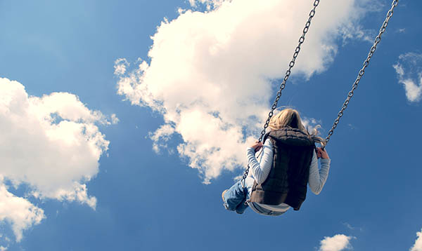 Girl swinging in the clouds