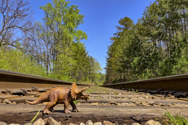 Toy dinosaur on railroad tracks