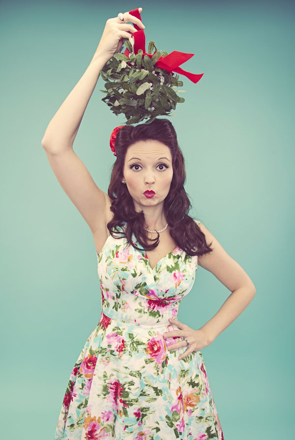 Woman holding mistletoe over her head