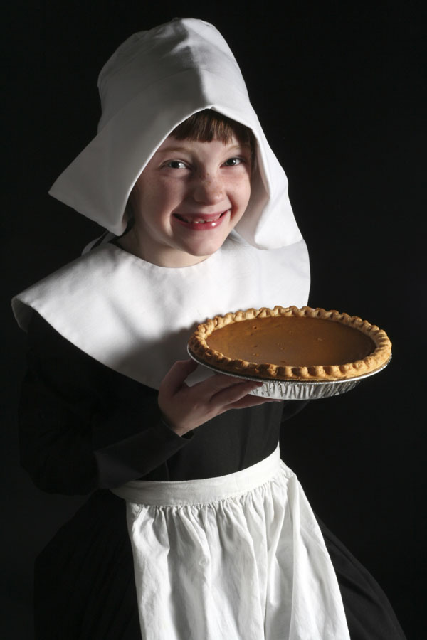 Girl dressed as a thanksgiving pilgrim, holding a pumpkin pie