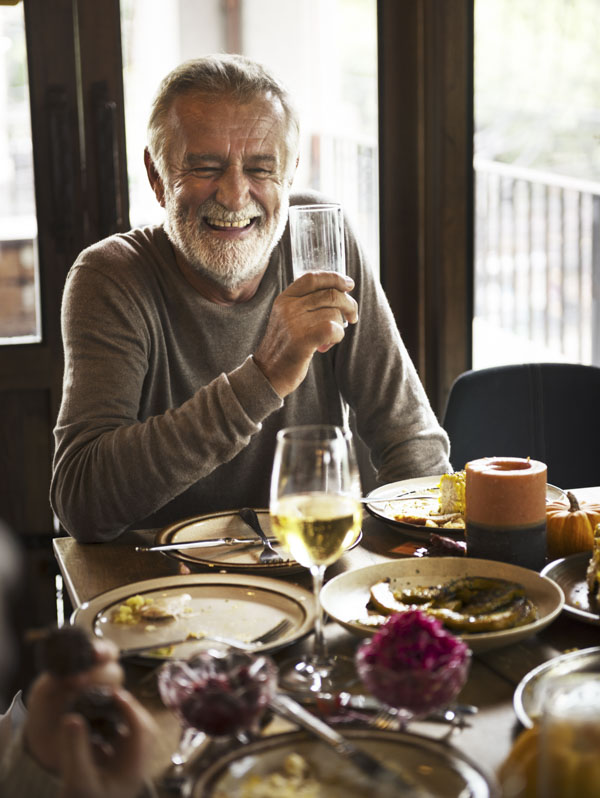 Man laughing at Thanksgiving dinner table