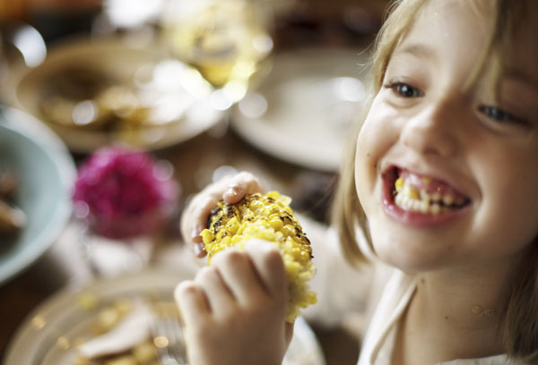 Little girl with corn in her teeth