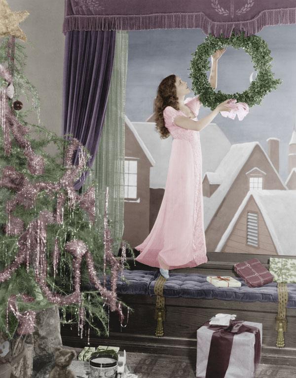 Vintage girl hanging wreath in window