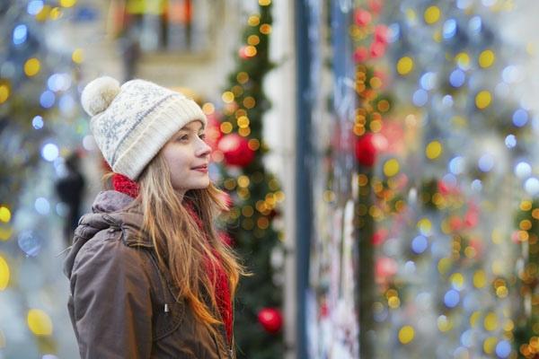 Woman looking in store window at Christmas