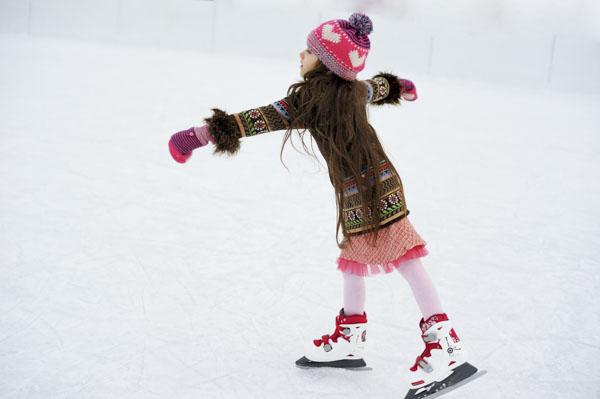 Girl ice skating on pond