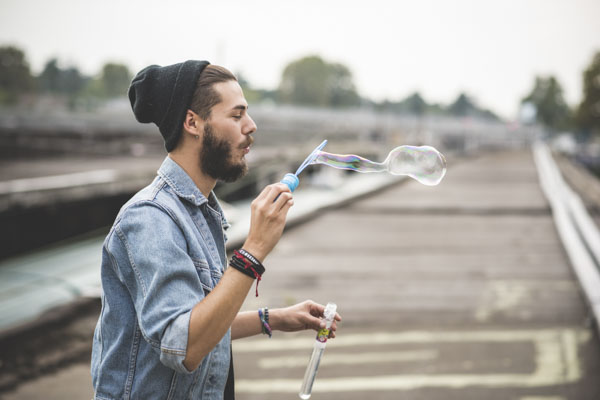 Man blowing into bubble wand