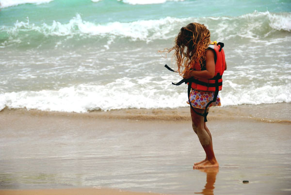 Girl putting on life jacket at ocean