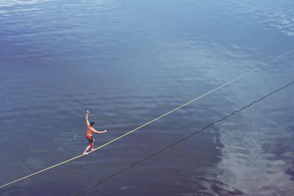 Man walking on tightrope over ocean