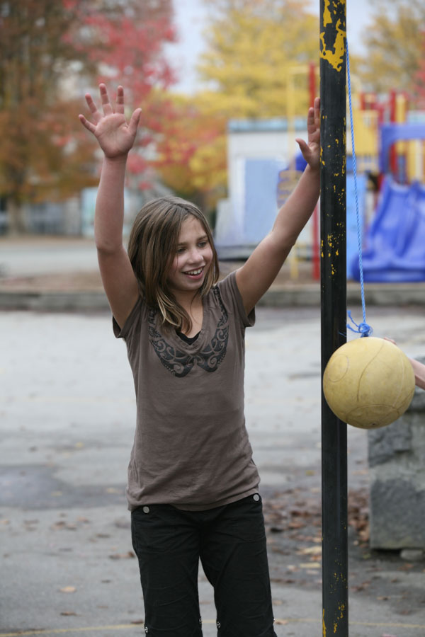 Girl with arms raised claiming the win at tether ball