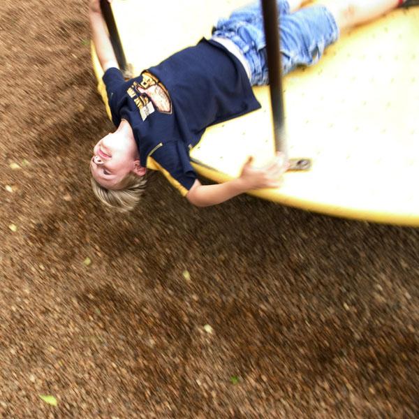 Child spinning on playground merry-go-round