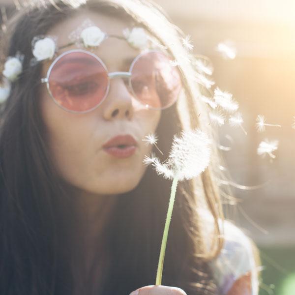 Bohemian woman blowing on a dandelion
