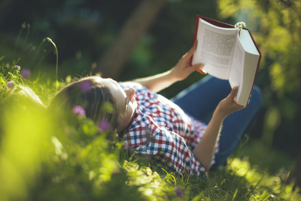 Woman on her back in field of flowers reading book