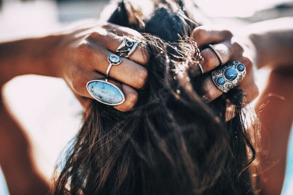 Woman with rings on her fingers holding her head
