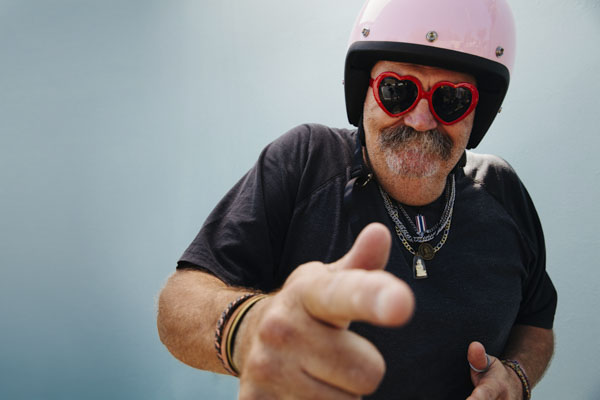 Grandpa in pink motorcycle helmet and red heart shaped sunglasses pointing at camera