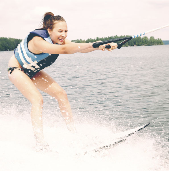 Girl on water skis laughing