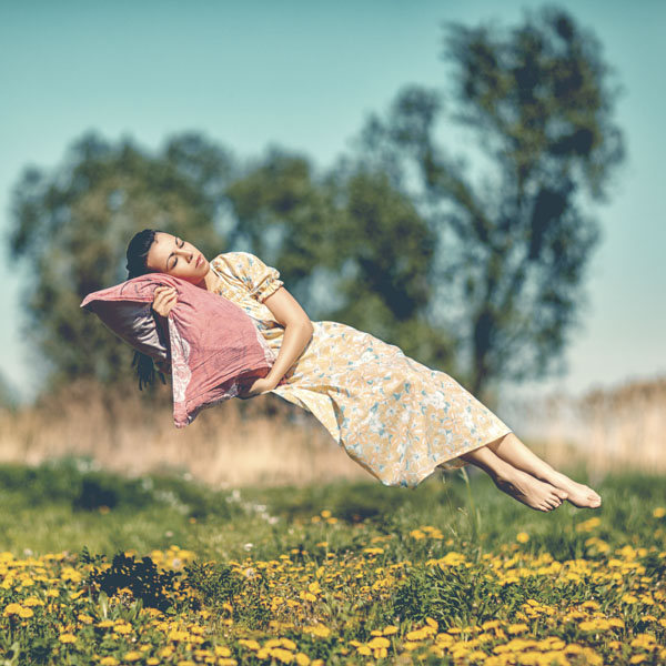Woman flying over meadow in her dreams