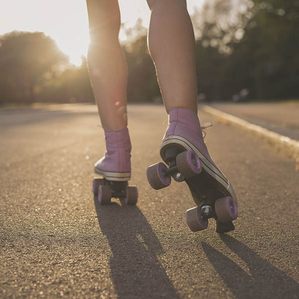 Woman on roller skates skating down road