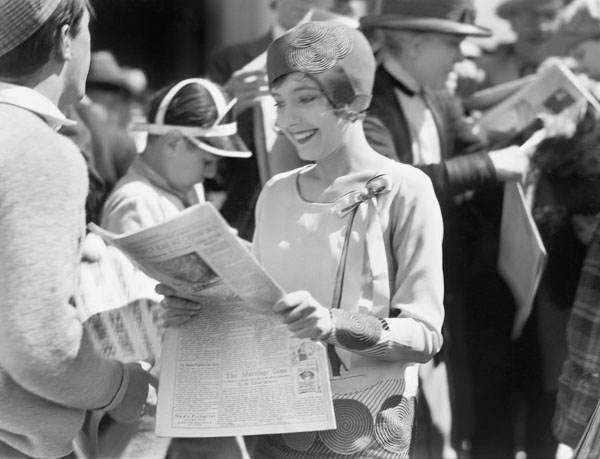 Vintage woman smiling as she reads the newspaper
