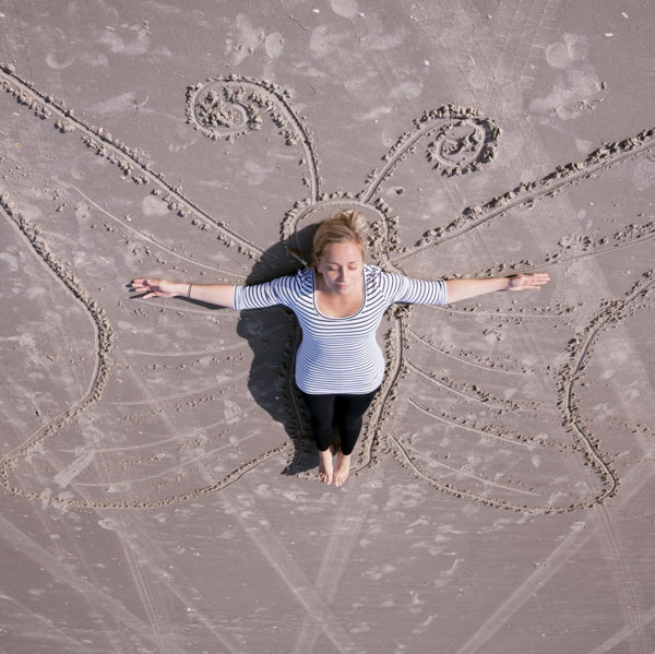 Woman with arms spread wide on chalk butterfly