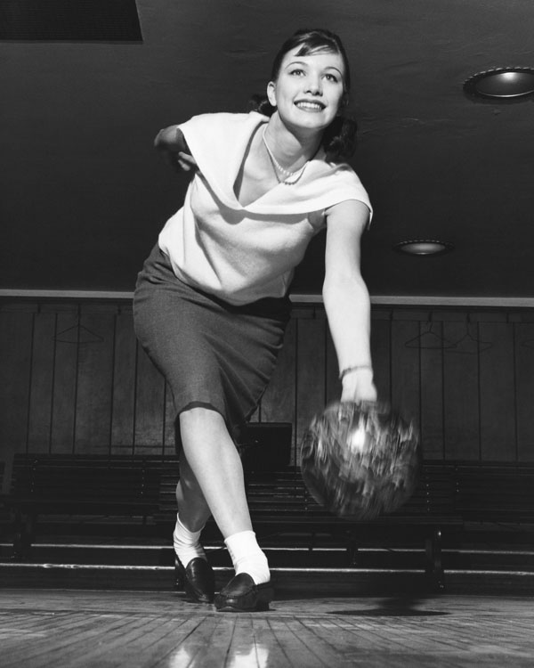 Retro woman with smile bowling for spare
