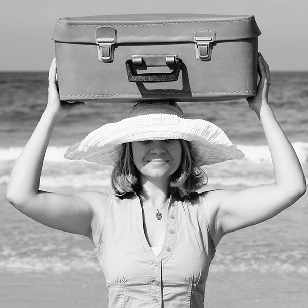 Happy woman holding suitcase on her head