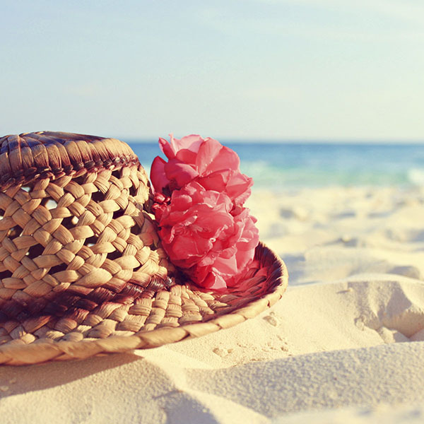 Straw hat with flower on the beach