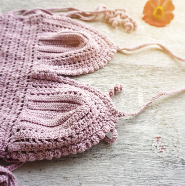 Pink crocheted halter top on table