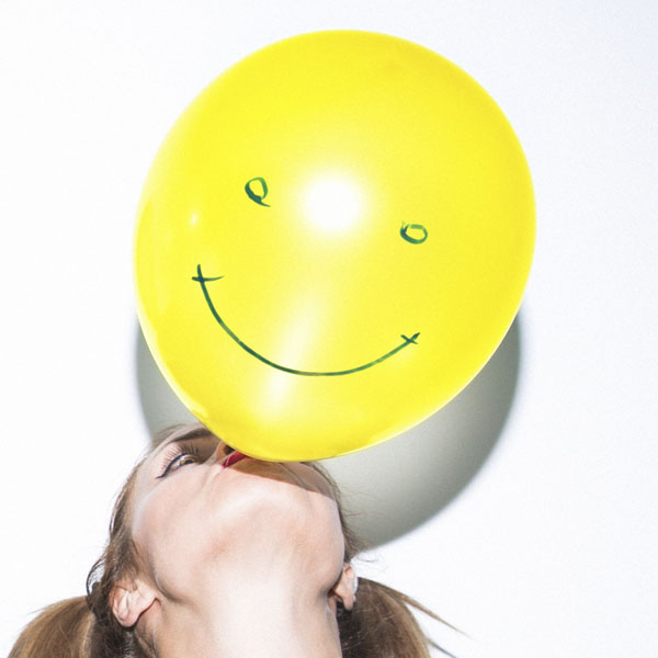 Girl blowing up happy face balloon