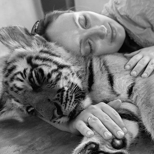 Young woman hugging baby tiger