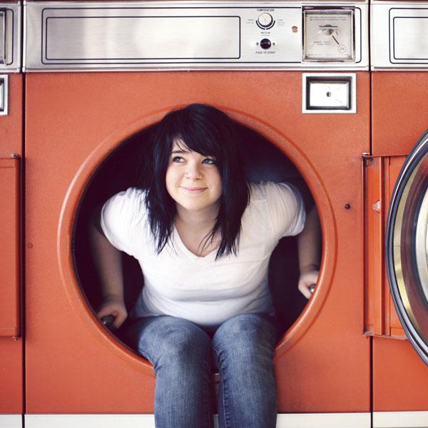 girl sitting in laundromat washing machine