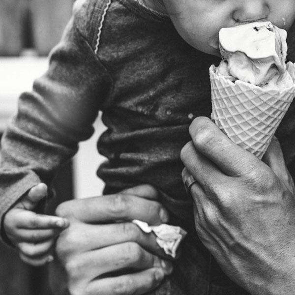 Parent offering bite of ice cream cone to child