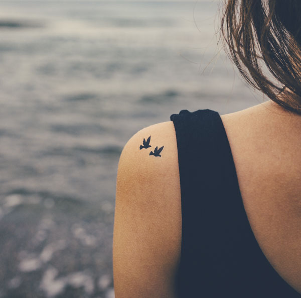 Woman with bird tattoos on her shoulder